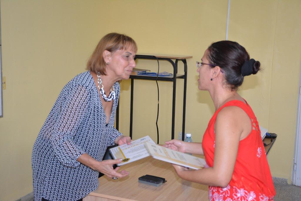 La Dr. C. Aniuska Ortiz Pérez, Jefa del Departamento de Calidad de la UHo, entrega el Reconocimiento a la Dr. C. Ileana Capote Padrón por su participación en la evaluación externa a la Maestría en Dirección. UHO FOTO/Luis Ernesto Ruiz Martínez
